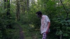 Horrible zombie runs into the forest and looking for the victim Stock Footage