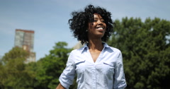 Young adult black woman in city park walking smiling happy face Stock Footage