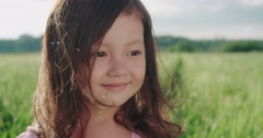 Little Asian girl standing in a green field of young wheat,close-up, flowing Stock Footage
