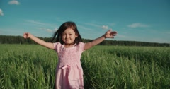 Little Asian girl running in a green field of young wheat,slow motion Stock Footage