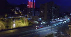 Rising up alongside the light up Torre Colpatria in Bogota at night Stock Footage