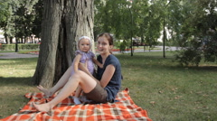 A young nanny sitting on a blanket and tossing a baby girl upwards Stock Footage