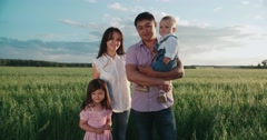 Portrait of young happy Asian family standing in a green field with two children Stock Footage