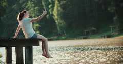 A woman relaxes on the shore of the lake, sitting on the edge of the wooden pier Stock Footage