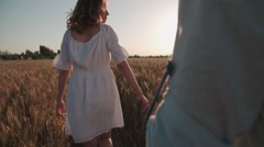 Follow me, young beautiful girl with her boyfriend runs across the field of Stock Footage