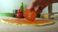 Man putting tomato slices over pizza base. Cooking, part of the set. 4K close up Stock Footage