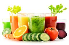 Glasses with fresh organic vegetable and fruit juices isolated on white. Deto Stock Photos