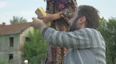 Man cutting bread with knife and giving to young girl, tilt up and tilt down. Stock Footage