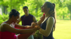 Female runner doing stretching exercise. Multiethnic friends stretching outdoor Stock Footage