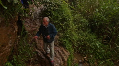 Old Man Picks Way along Path in Tropical Forest Stock Footage