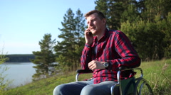 Man sitting in a wheelchair and talking on the phone on the shore Stock Footage