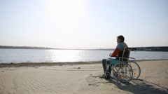 Man sitting in a wheelchair on the shore Stock Footage