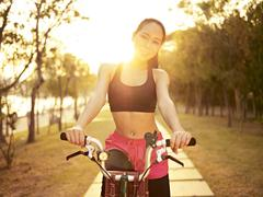 Young asian woman riding bike outdoors at sunset Stock Photos