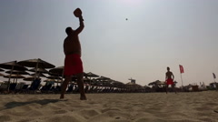 Two men silhouette playing beach tennis on the beach Stock Footage