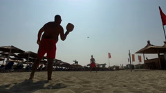 Father and son silhouettes playing tennis together on the beach Stock Footage
