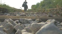 Refugees walking across the railway line and passing over the camera, low angle. Stock Footage