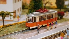 Model trains transit and a tram departs on a diorama, close up Stock Footage