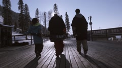 Back side of three skiers walk on wooden road on ski resort. Sun beams. Snow Stock Footage