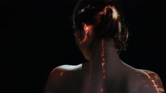 4K Light projected onto woman's back indicating brain activity or pain Stock Footage