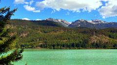 4K Green Mountain Lake, Forest Hillside and Blue Sky Background, Turquoise Water Stock Footage