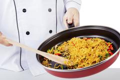 Chef cooking noodle with a pan Stock Photos