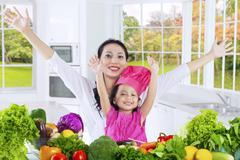 Child and mother with vegetables in kitchen Stock Photos