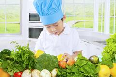 Child prepares fresh vegetables in kitchen Stock Photos