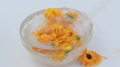 Water flow Struth in a bowl with flowers of calendula Stock Footage