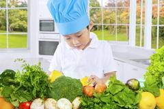Male child preparing healthy vegetables Stock Photos