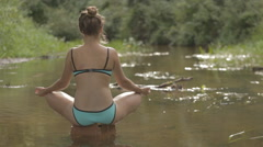 Beautiful girl meditates on water in the middle of the forest river Stock Footage