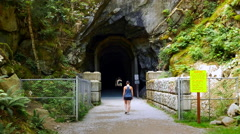 4K Woman Walks into Train Tunnel, Gravel Path, Othello Tunnels, Hope BC Canada Stock Footage