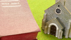 Slider shot across a model church and an old bible. Stock Footage