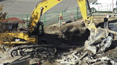 Excavator moving metal debris in a construction site Stock Footage