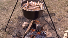 Cooking sausages in cast-iron cauldron Stock Footage