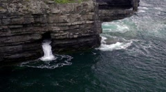 Waves issuing from a sea cave at the Bridges of Ross on Ireland's Atlantic coast Stock Footage