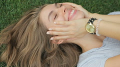 Young , attractive girl lying on the grass enjoying the outdoors Stock Footage