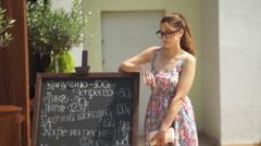 The girl near a street menu. Menu is written in Russian Stock Footage