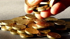 Fingers dropping £1 sterling coins into a pile. Stock Footage