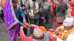 Hindu woman gets kalava thread around wrist by priest,Dakshinkali,Nepal Stock Footage
