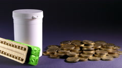 Tablets and pills leading to a pile of £1 sterling coins. Stock Footage