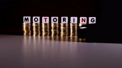 £1 sterling coins, 'motoring' in letters and model car. Stock Footage