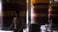 Buddhist devotee spinning giant prayer wheels,Pharping,Nepal Stock Footage