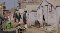 Woman and chicken in refugee tent camp,Bhaktapur,Nepal Stock Footage