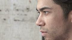 Thoughtful and sad young man looking in front of him: side closeup portrait  Stock Footage