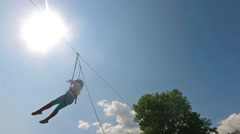 Little child on zip line against sun, SLOW MOTION Stock Footage