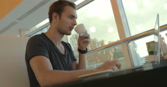 Adult man in a cafe looks a feed on a laptop and drinking coffee Stock Footage