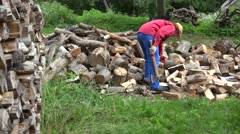 Worker man split log near wood pile in garden at summertime. 4K Stock Footage