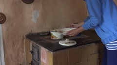 Wench woman take cooked dumplings from boiling pot on furnace stove. 4K Stock Footage