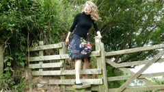 Pretty young woman climbing over a stile – front view. Stock Footage