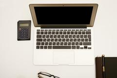 Computer, calculator, notepad on the table top Stock Photos